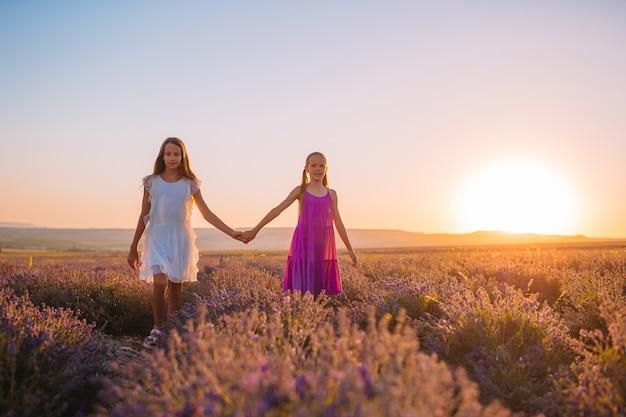 Kinderen in lavendel bloemen veld bij zonsondergang in de jurken Premium Foto