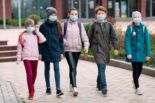 Kinderen in medische maskers verlaten de school. Premium Foto
