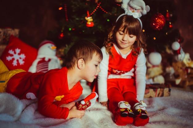 Kinderen in rode kleren zitten voor een kerstboom Gratis Foto
