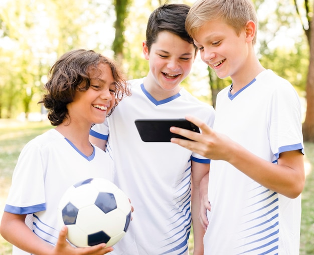 Kinderen in sportkleding kijken naar een telefoon Gratis Foto