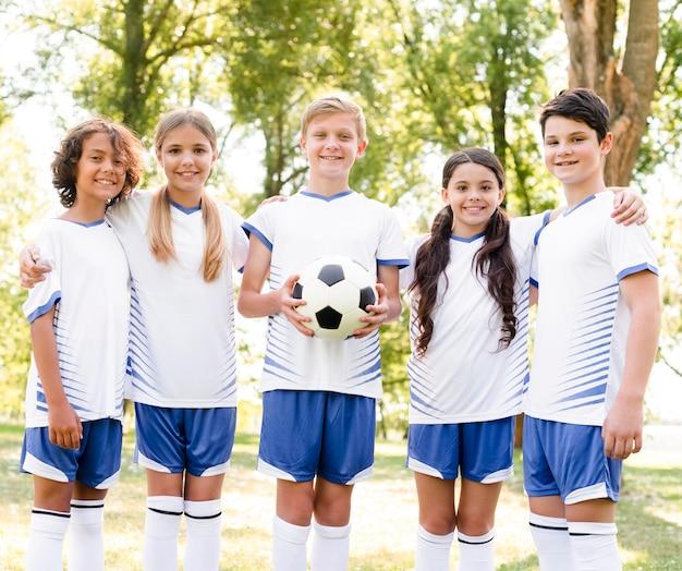 Kinderen in sportkleding voetballen Gratis Foto
