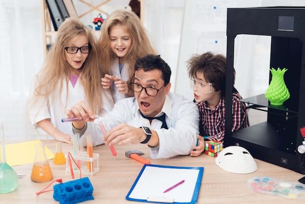 Kinderen in witte jassen doen tijdens de les een chemisch experiment Premium Foto