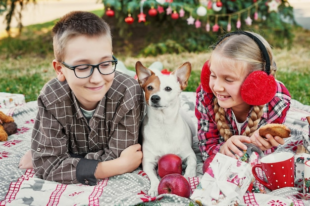 Kinderen jongen en meisje met een hond jack russell terrier in de buurt van een kerstboom met geschenken, Premium Foto