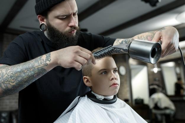 Kinderen kapper snijden kleine jongen in een kapperszaak Gratis Foto