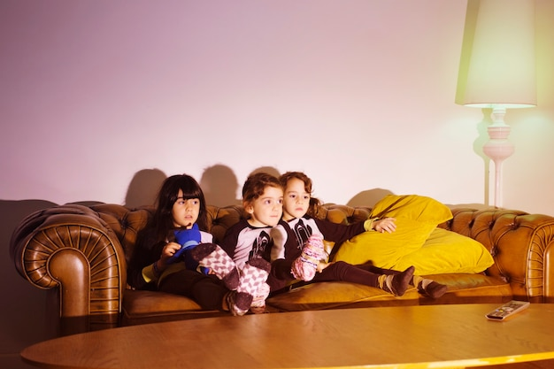 Kinderen kijken naar film op de bank Gratis Foto
