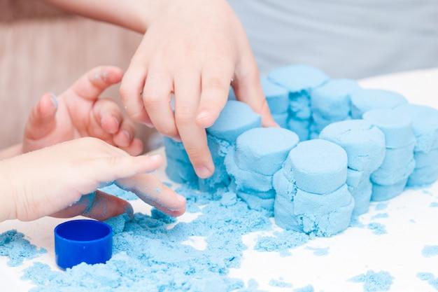 Kinderen maken figuren van blauw kinetisch zand Premium Foto