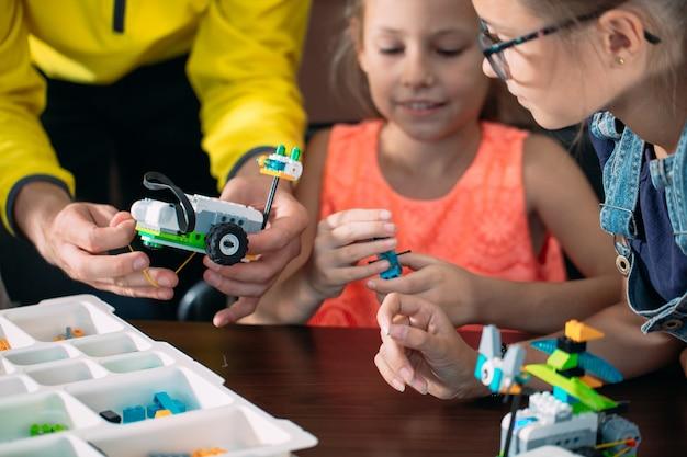 Kinderen maken robots met leraar. vroege ontwikkeling, diy, innovatie, moderne technologie. Premium Foto