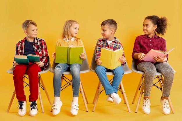 Kinderen met boeken kijken naar elkaar Gratis Foto