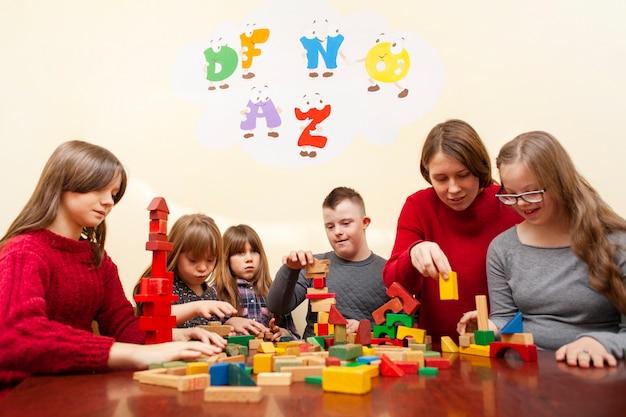 Kinderen met het syndroom van down spelen met kleurrijke blokken Premium Foto