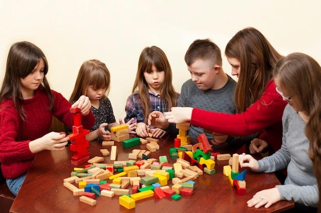 Kinderen met het syndroom van down spelen met vrouw en speelgoed Premium Foto