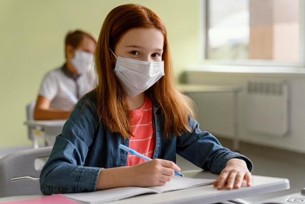Kinderen met medische maskers die op school studeren Gratis Foto