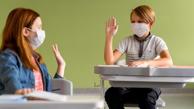 Kinderen met medische maskers geven elkaar op afstand een high-five Gratis Foto