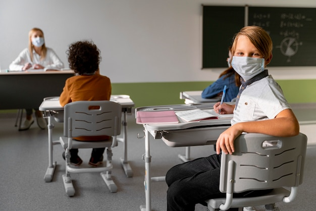 Kinderen met medische maskers leren op school met vrouwelijke leraar Gratis Foto