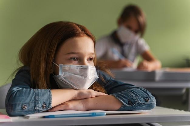 Kinderen met medische maskers luisteren naar leraar in de klas Gratis Foto