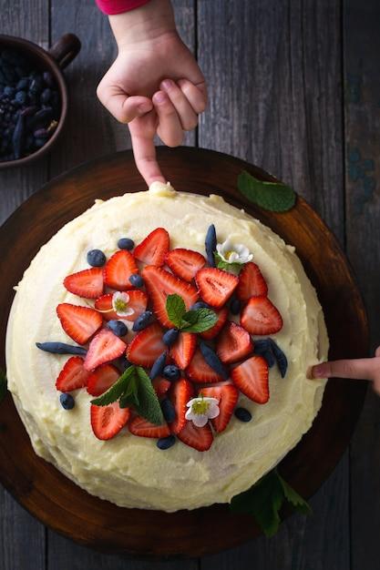 Kinderen proberen cake met aardbeien Premium Foto