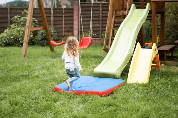 Kinderen rijden van de glijbaan, zussen spelen samen in de tuin Gratis Foto