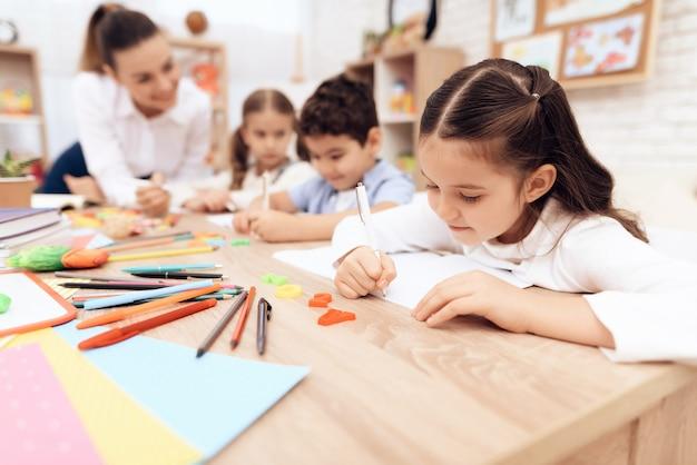 Kinderen schrijven in notitieboekjes met een pen. Premium Foto
