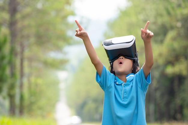 Kinderen spannende kijken naar virtual reality box bril op wazig boom Premium Foto