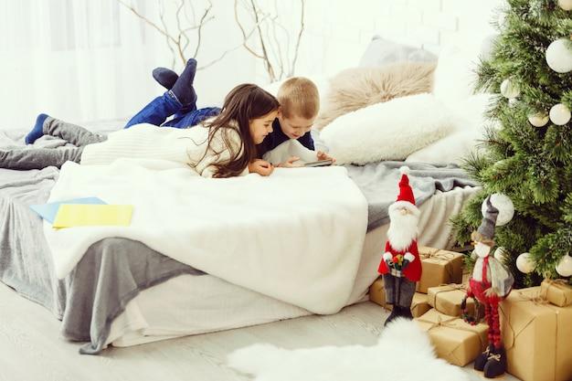 Kinderen spelen in bed van de ouders in de winter Premium Foto