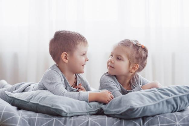 Kinderen spelen in bed van de ouders. kinderen worden wakker in een zonnige witte slaapkamer. jongen en meisje spelen in bijpassende pyjama. nachtkleding en beddengoed voor kinderen en baby's. kinderkamer interieur voor peuter kind. familie ochtend Premium Foto