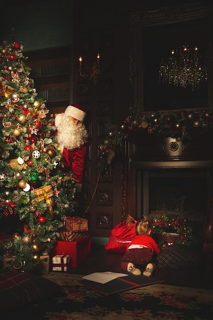 Kinderen spelen in de buurt van de kerstboom. de echte kerstman houdt ze in de gaten. Premium Foto