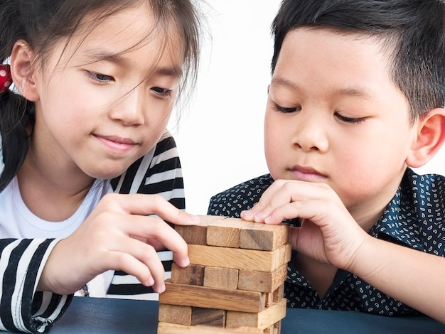Kinderen spelen jenga, een houten blokken torenspel Gratis Foto