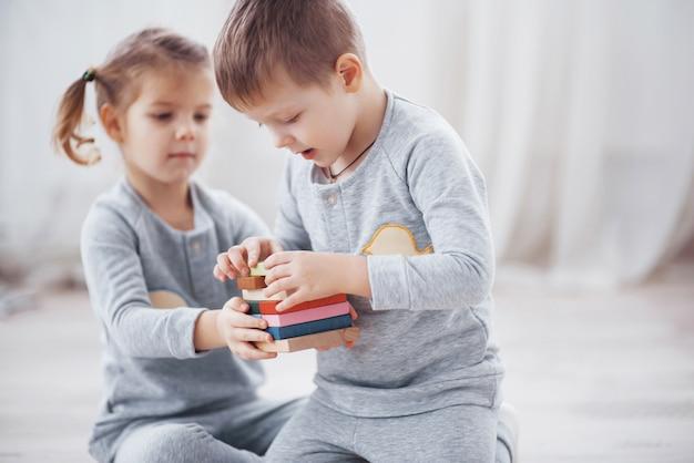 Kinderen spelen met een speelgoedontwerper op de vloer van de kinderkamer. Premium Foto