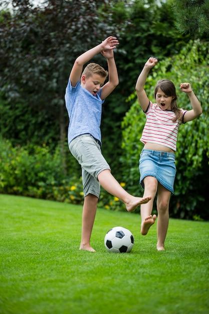 Kinderen spelen met voetbal in park Premium Foto