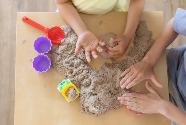 Kinderen spelen samen met kinetisch zand en zandvormen Premium Foto