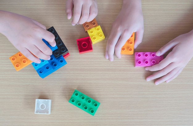 Kinderen spelen stukjes plastic creatieve constructie blokken Gratis Foto