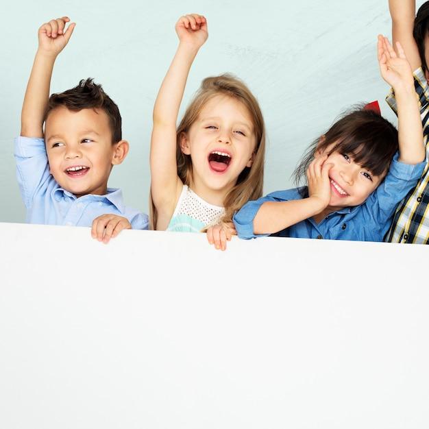Kinderen verhogen armen juichen met mockup bord Gratis Foto