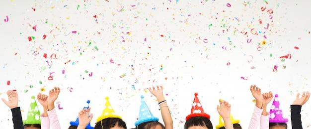 Kinderen verhogen handen in partij geniet van het gooien van kleurrijke confetti in kerstmis nieuwjaar Premium Foto