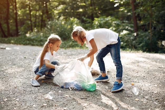Kinderen verzamelt afval in vuilniszakken in park Gratis Foto