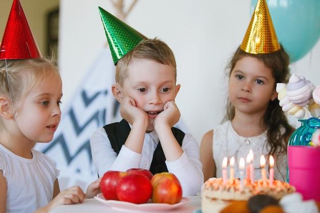 Kinderen vieren hun verjaardag met een taart met kaarsjes Premium Foto