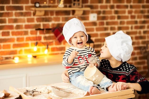 Kinderen worden gekookt en gespeeld met meel en deeg in de keuken Premium Foto