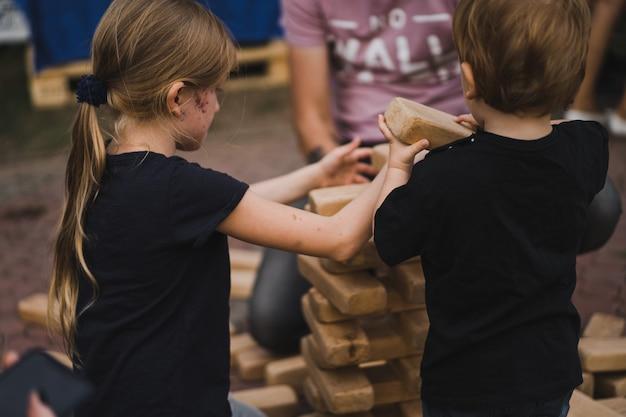 Kinderen zetten een piramide van kubussen Gratis Foto