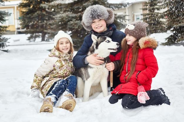 Kinderen zitten in de sneeuw en streelden hond husky. kinderen gaan in de winter uit met husky's Premium Foto