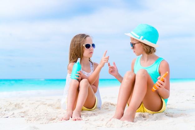 Kinderen zonnebrandcrème op elkaar toepassen op het strand. het concept van bescherming tegen ultraviolette straling Premium Foto