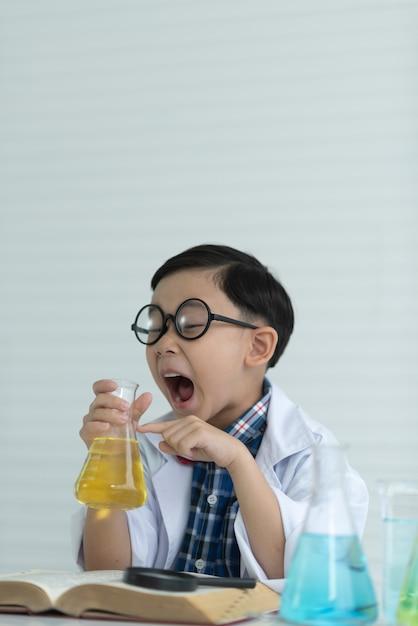 Kinderenjongen die de chemische oplossing in het laboratorium bestudeert dat een glaswerk gebruikt. Premium Foto