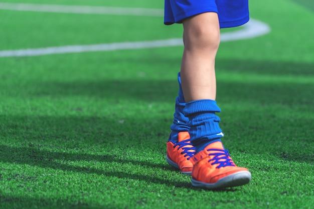 Kinderenvoeten met voetbalschoenen die op opleidingskegel op voetbalgrond opleiden Premium Foto
