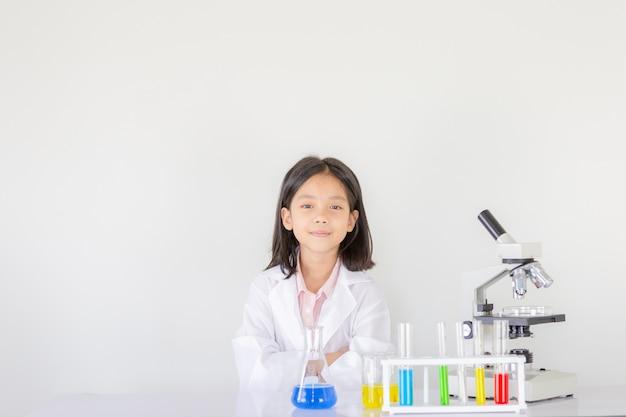 Kinderenwetenschap, het gelukkige meisje spelen die chemische experimenten doen in het laboratorium Premium Foto