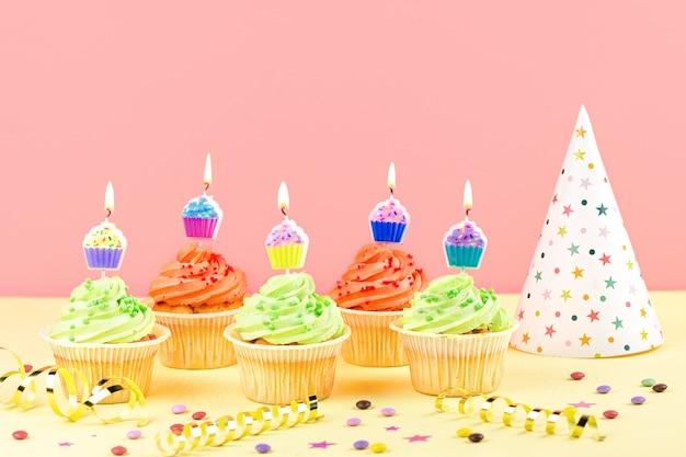 Kinderfeestje accessoires - kleurrijke cupcakes met brandende kaarsen, feestmuts, slingers, confetti. kopieer ruimte Premium Foto