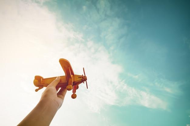Kinderin inspiratie - handen van kinderen die een speelgoedvliegtuig hebben en dromen willen een piloot zijn - vintage filter effect Premium Foto