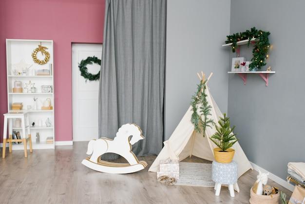 Kinderkamer, versierd voor kerstmis op roze en grijs Premium Foto