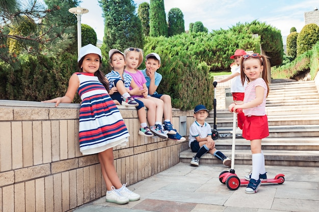 Kindermode concept. groep tiener jongens en meisjes poseren in het park. kleurrijke kinderkleding, lifestyle, trendy kleurenconcepten. Gratis Foto