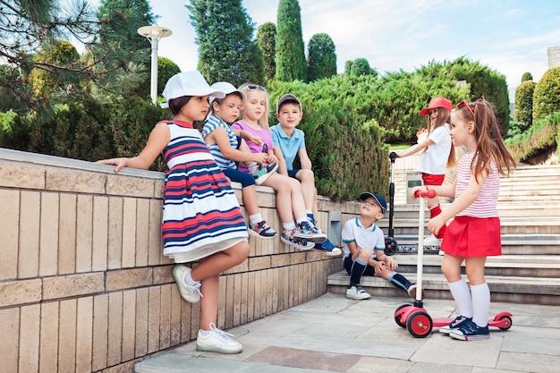 Kindermode concept. groep tiener jongens en meisjes poseren in het park Gratis Foto