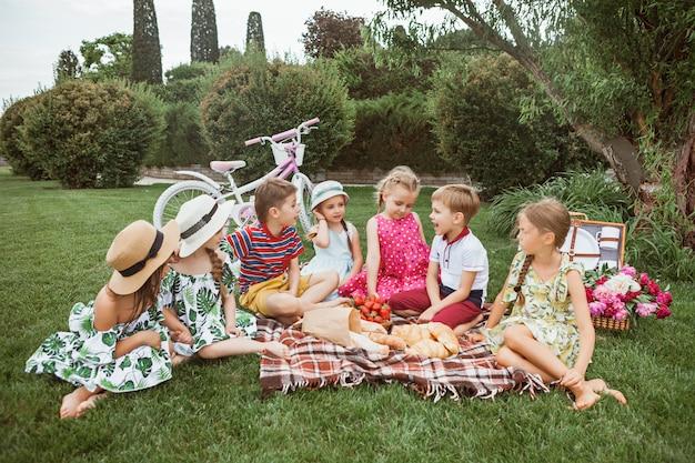 Kindermode concept. groep tiener jongens en meisjes zitten op groen gras in het park Gratis Foto