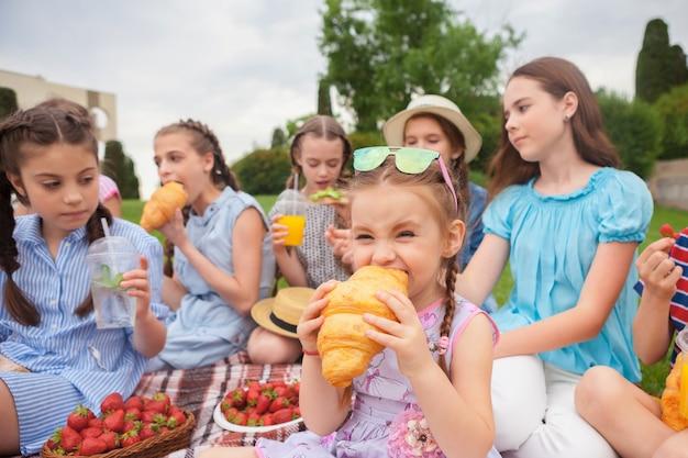 Kindermode concept. groep tiener meisjes zitten op groen gras in het park. kleurrijke kinderkleding, lifestyle, trendy kleurenconcepten. Gratis Foto
