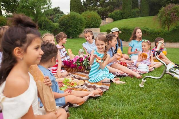 Kindermode concept. groep tienermeisjes zittend op groen gras in het park Gratis Foto