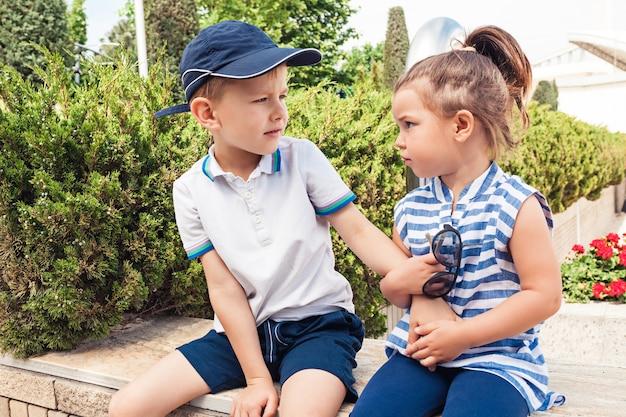 Kindermode concept. tienerjongen en meisjeszitting bij park. kleurrijke kinderkleding, lifestyle, trendy kleurenconcepten. Gratis Foto